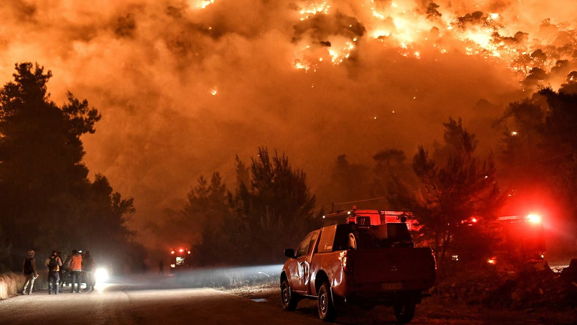 Flames rise as firefighters and volunteers try to extinguish a fire burning in the village of Schinos, near Corinth, Greece, May 19, 2021. Picture taken May 19, 2021. (Reuters)