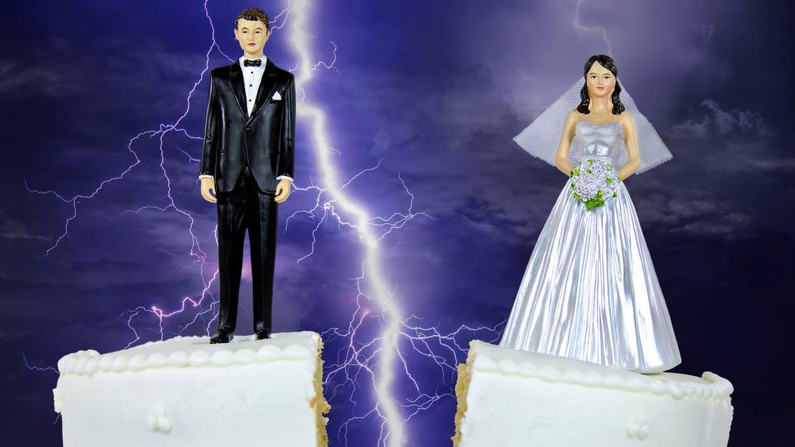Bride and groom on split wedding cake stock photo