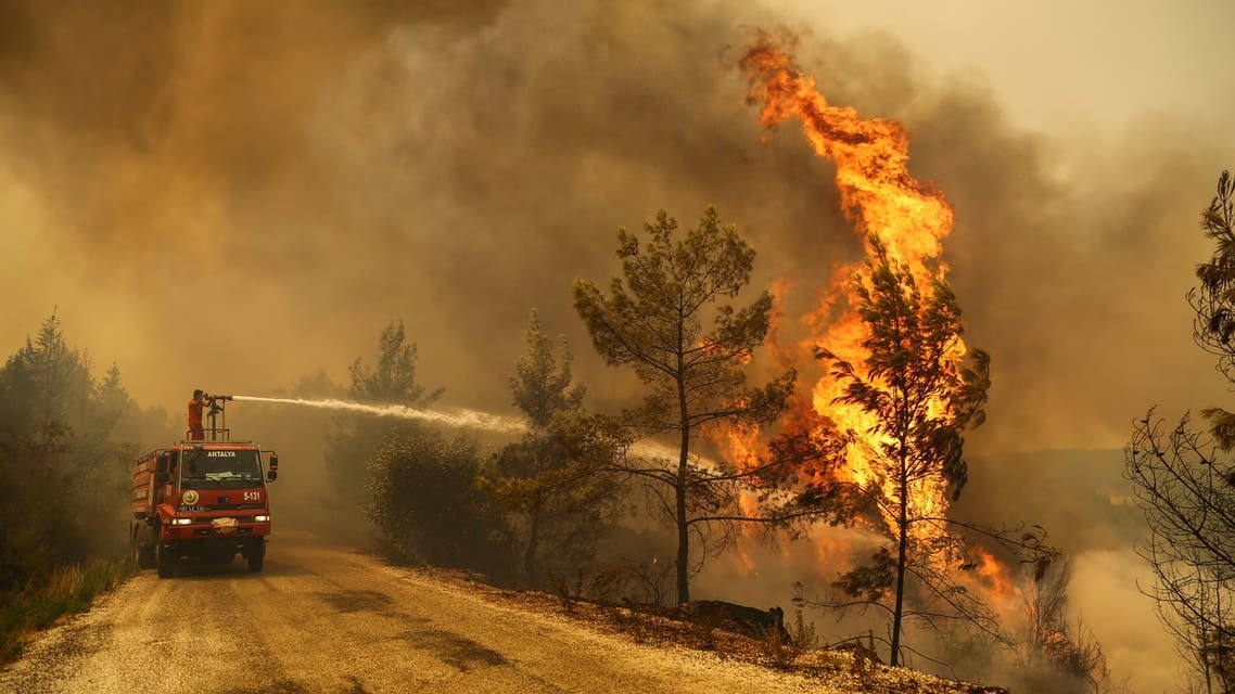 A firefighter extinguishes a forest fire near the town of Manavgat, east of the resort city of Antalya, Turkey, July 30, 2021. REUTERS/Kaan Soyturk