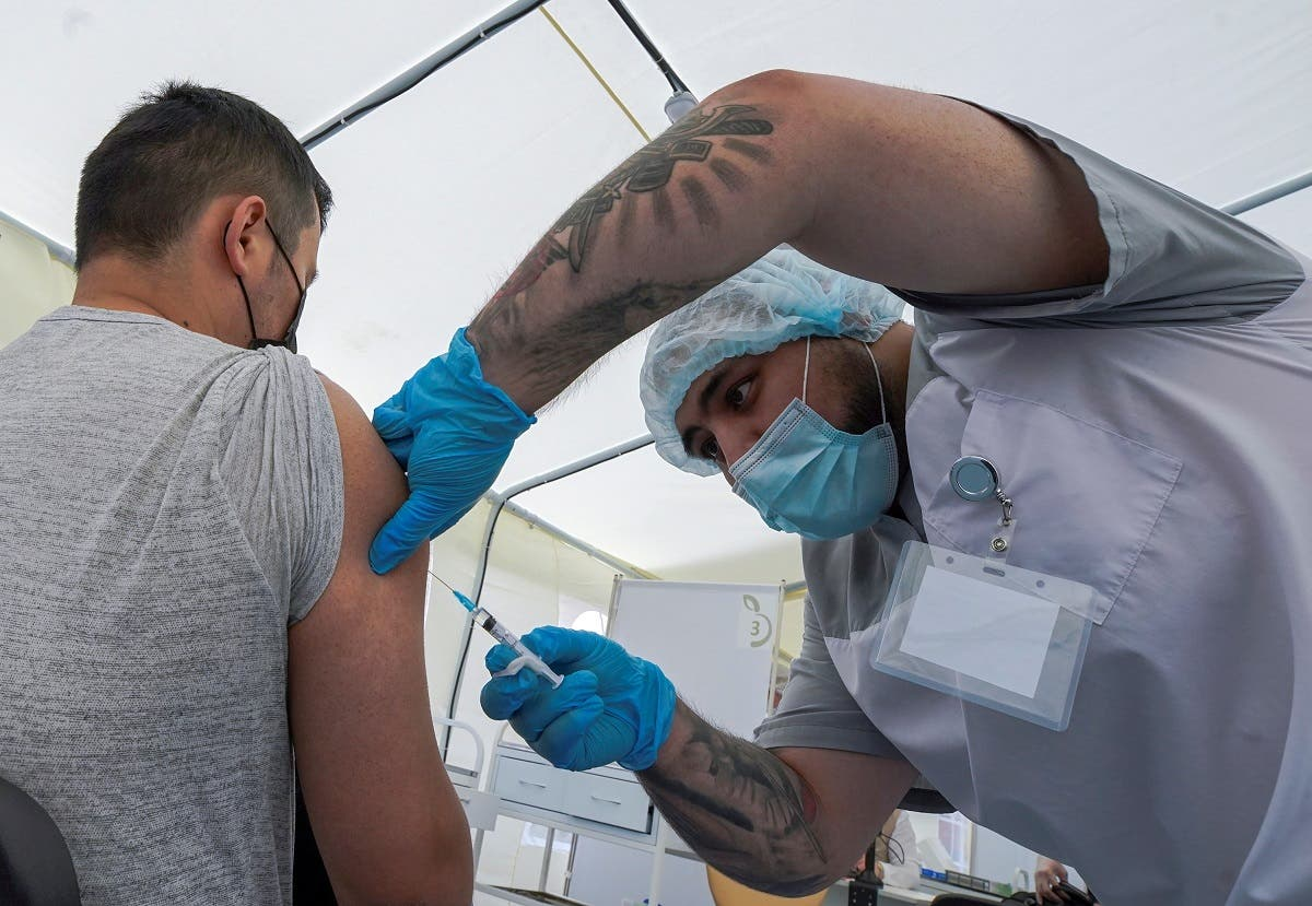 A migrant worker receives a jab while being injected with the one-dose Sputnik Light vaccine against the coronavirus  in a vaccination center at a city market in Moscow, Russia, on June 30, 2021. (Reuters)