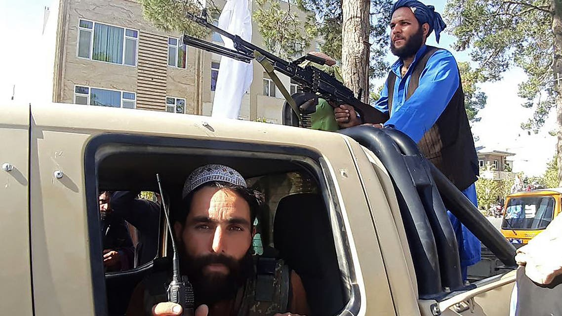 Taliban fighters are pictured in a vehicle along the roadside in Herat, Afghanistan's third biggest city, after government forces pulled out the day before following weeks of being under siege.