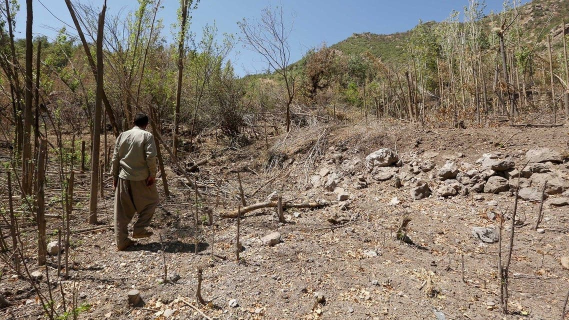 File photo of a resident walking past a crater caused by a Turkish airstrike against Kurdistan Workers Party (PKK) in Sigire on the outskirts of Dohuk province. (Reuters)