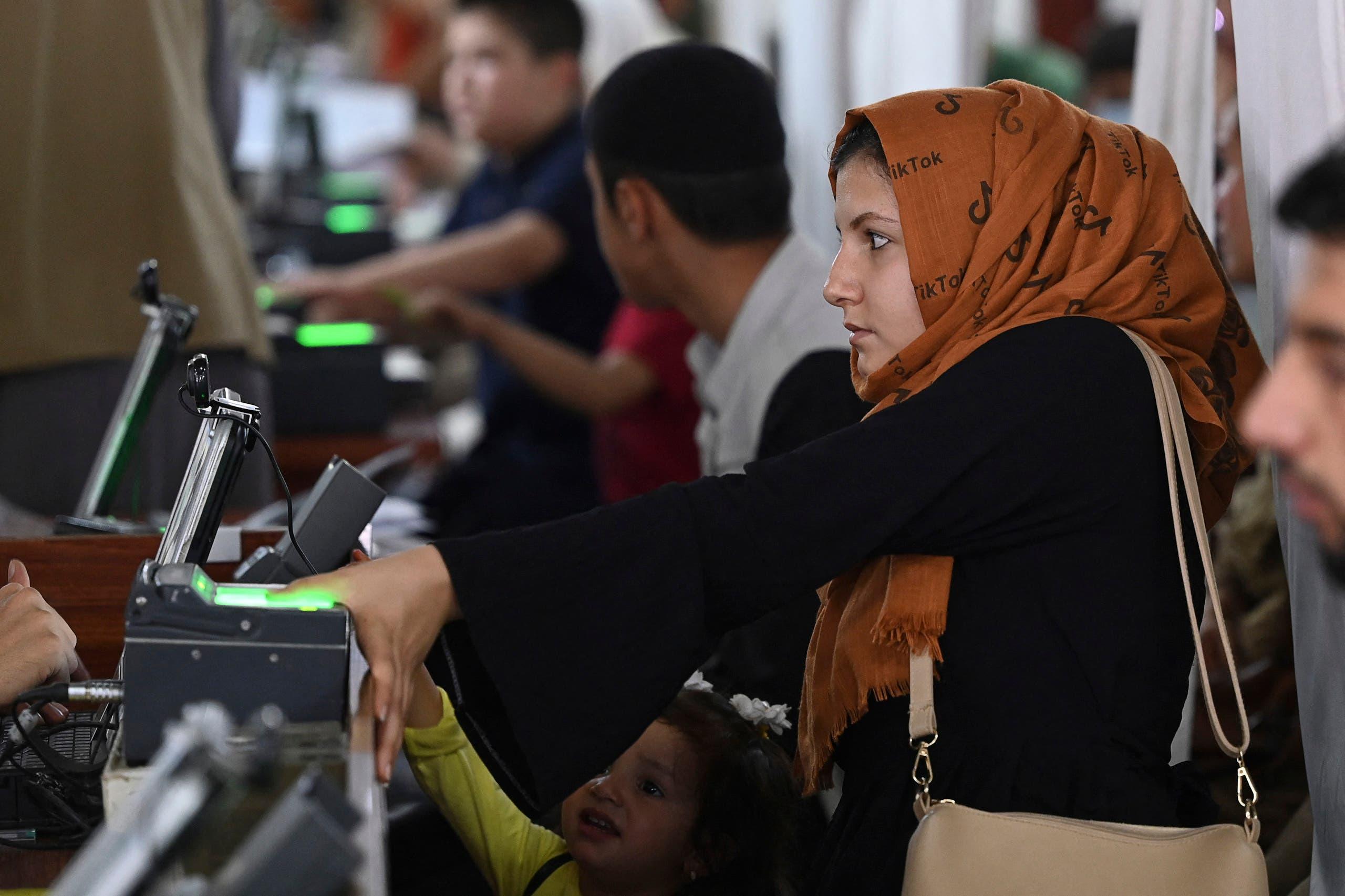 سيدة أفغانية تعطي بصماتها للحصول على جواز سفر وسط تقدم طالبان في البلاد