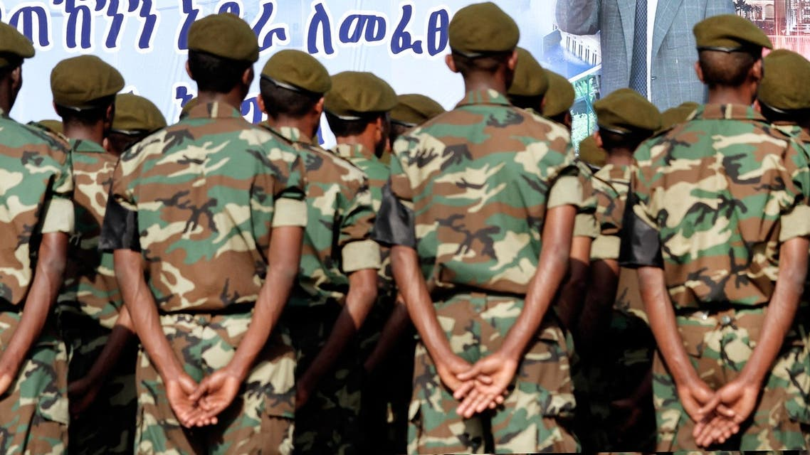 Soldiers take part to the official state funeral of Ethiopia's late Prime Minister Meles Zenawi under a giant poster of late strongman on September 2, 2012 in Addis Ababa. Tens of thousands of Ethiopians and many African leaders mourned the late strongman and long-serving prime minister, who died on August 20, 2012 at age 57, at the first state funeral for a leader of the Horn of Africa nation in over 80 years. AFP PHOTO/ MULUGETA AYENE