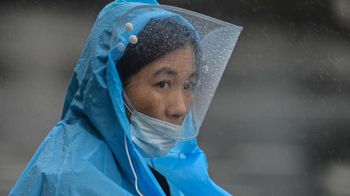 A woman wearing a raincoat and plastic covering walks in the rain along a street in Ningbo on July 25, 2021, as Typhoon In-Fa lashes the eastern coast of China. (File photo: AFP)