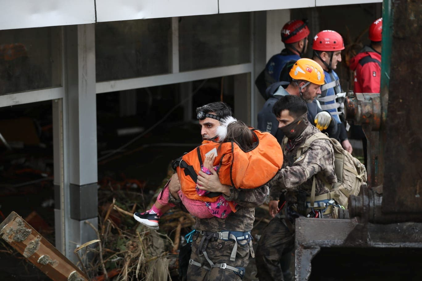 Search and Rescue team members evacuate a girl during flash floods which have swept through towns in the Turkish Black Sea region, in Bozkurt, a town in Kastamonu province, Turkey, August 12, 2021. (Reuters)