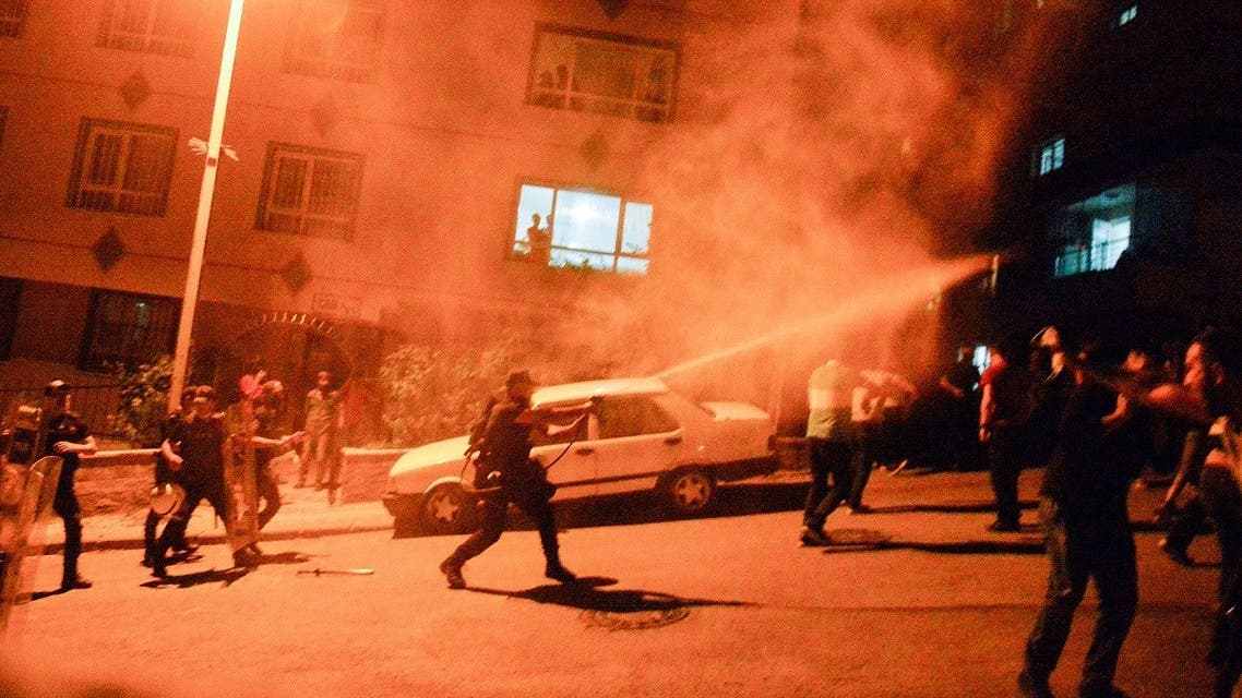 Turkish police use tear gas to disperse men who smash up shops and homes, believed to be owned by Syrian families, during an unrest, which broke out in response to a fight between locals and migrants in which one Turkish national was stabbed to death, in Ankara, on August 12, 2021, overnight. (AFP)