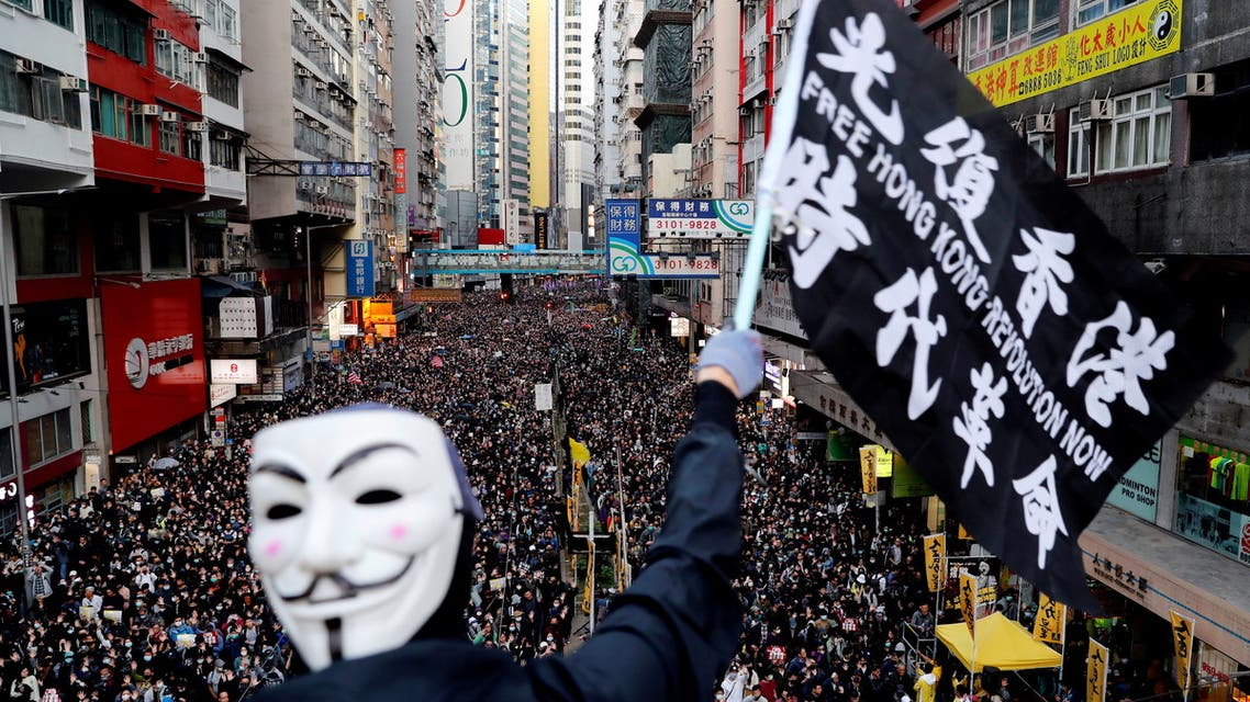 A protester wearing a Guy Fawkes mask waves a flag during a Human Rights Day march, organised by the Civil Human Right Front, in Hong Kong, China December 8, 2019. (File Photo: Reuters)