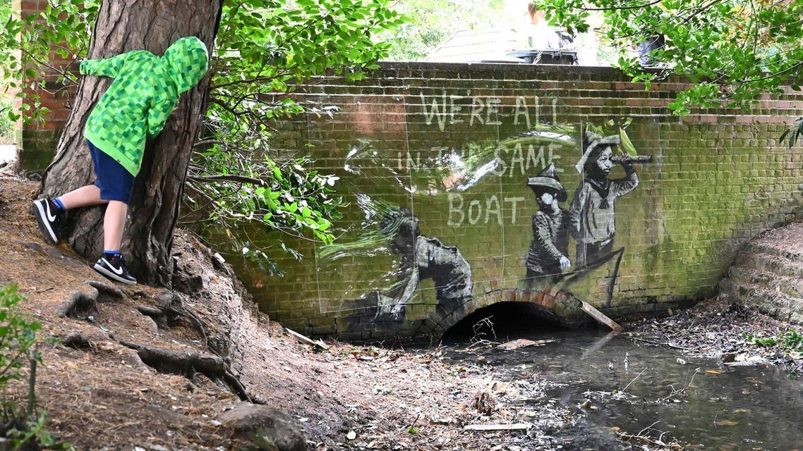 (FILES) In this file photo taken on August 08, 2021 A stensil of children playing at being sailors is the subject of a graffiti artwork bearing the hallmarks of street artist Banksy on the wall of a bridge in Everitt Park in Lowestoft on the East coast of England on August 8, 2021. Banksy, Britain's most famous street artist, on August 13 confirmed what many had already suspected -- that he is indeed the author of several works that have recently appeared in British seaside towns. An Instagram video clip just over three minutes long, and titled A Great British Spraycation, shows the elusive artist taking a summer road trip in a beat-up camper van and with cans of spray paint stashed in a cooler.