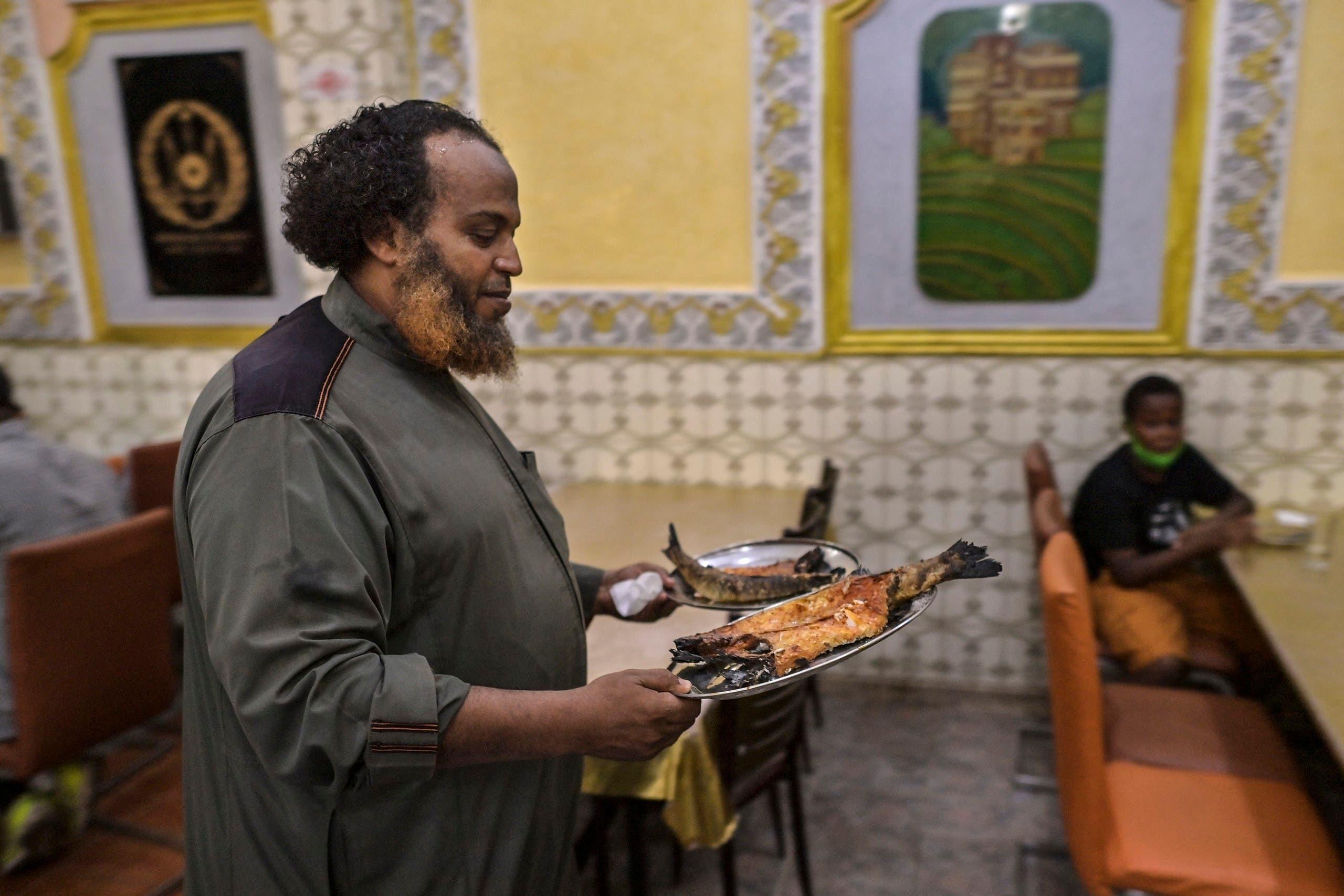 """عمر حمداني صاحب مطعم """"شي حمداني"""" يحمل طبقاً من السمك اليمني"""