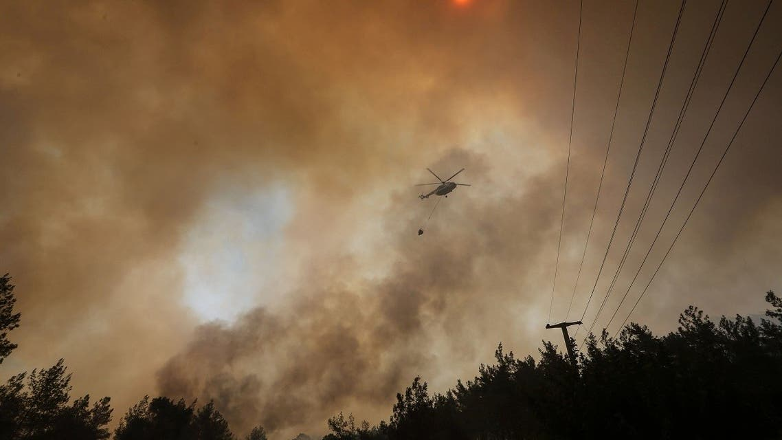 A firefighting helicopter returns from extinguishing a forest fire near Marmaris, Turkey, July 30, 2021. (Reuters/Kenan Gurbuz)