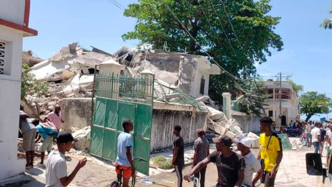People stand outside the residence of the Catholic bishop after it was damaged by an earthquake in Les Cayes, Haiti, August 14, 2021. (AP/Delot Jean)