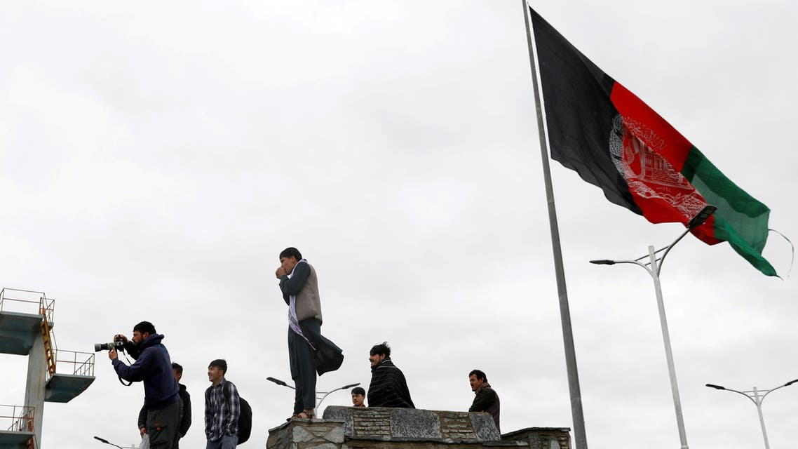 Youths take pictures next to an Afghan flag on a hilltop overlooking Kabul, Afghanistan, April 15, 2021. (Reuters)