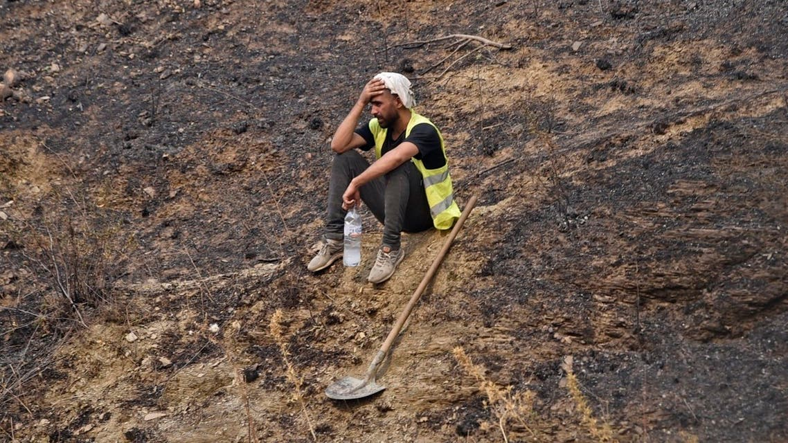 A volunteer rests after putting out a fire in the forested hills of the Kabylie region, east of the Algerian capital Algiers, on August 12, 2021. (Ryad Kramdi/AFP)