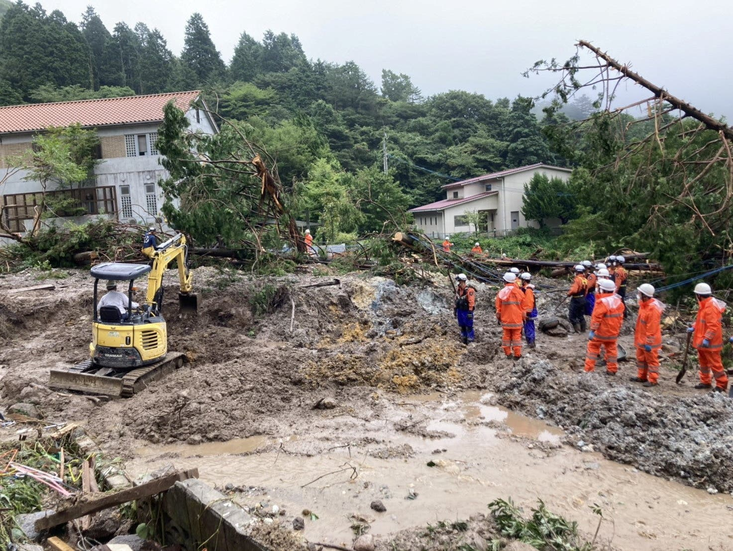 Rescue workers search for missing people at a landslide site caused by heavy rainfall in Unzen, Nagasaki Prefecture, southwestern Japan, in this handout image taken and released by Unzen City August 15, 2021. (Reuters)