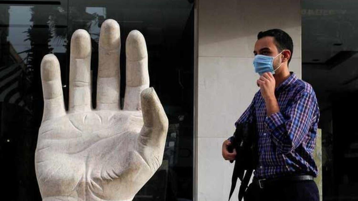 البطالة في مصر مناسبة رجل يرتدي كمامة واقية للوجه يسير بالقرب من رمز الجرانيت ويد السلام ، وسط مخاوف من مرض فيروس كورونا