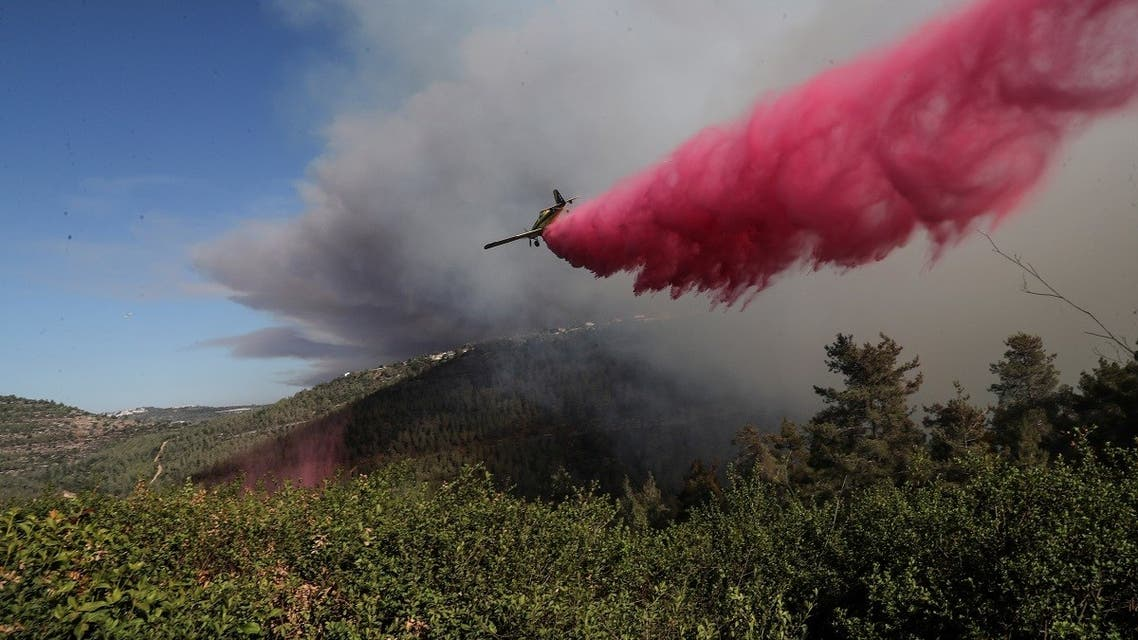 A firefighting plane disperses fire retardant as it assists in extinguishing a fire near the Israeli village of Shoresh at the outskirts of Jerusalem August 15, 2021. (Reuters/Ronen Zvulun)
