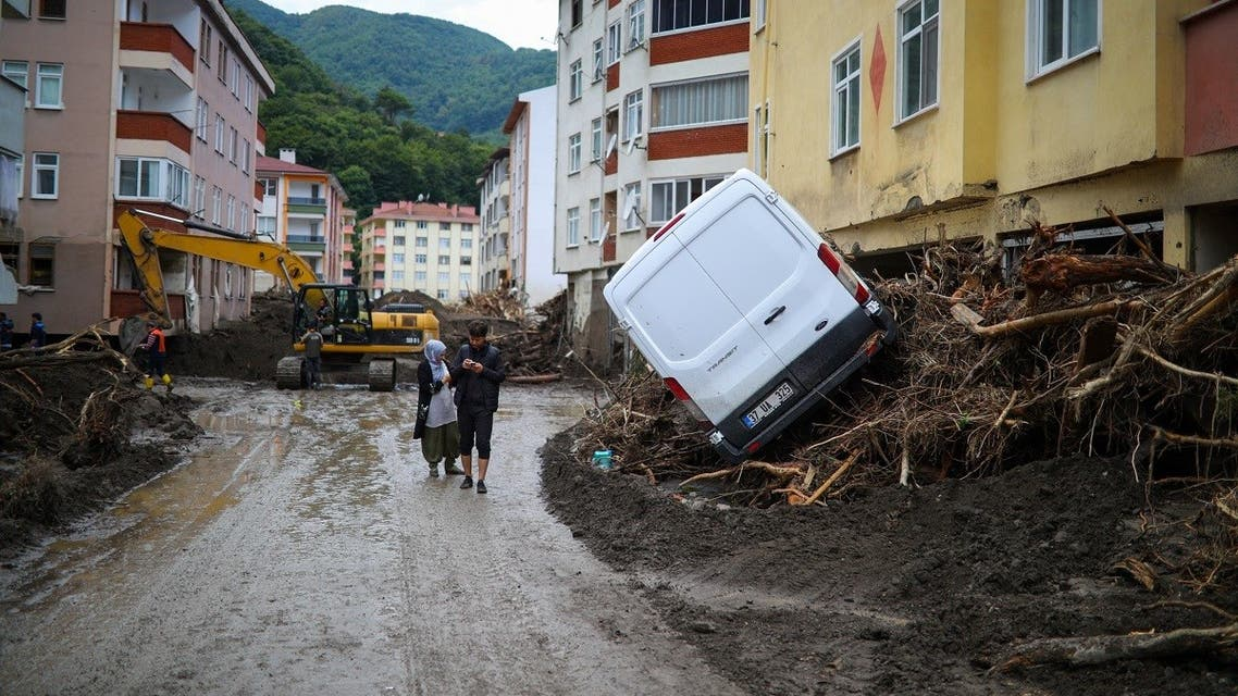 A man and woman walk along a muddy street after flash floods destroyed parts of Bozkurt in the district of Kastamonu, in the Black Sea region of Turkey on August 14, 2021. (STR/AFP)