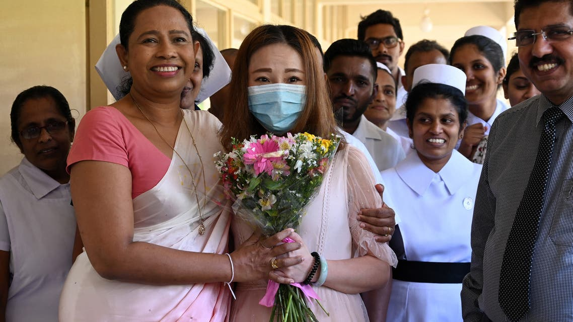 A Chinese tourist (C), who was tested positive for the COVID-19 coronavirus and isolated for treatment, poses for photographs with Sri Lankan Health Minister Pavithra Wanniarachchi (front L) and medical staff after she was discharged from the main infectious diseases hospital near Colombo on February 19, 2020, following her recovery. (File photo: AFP)