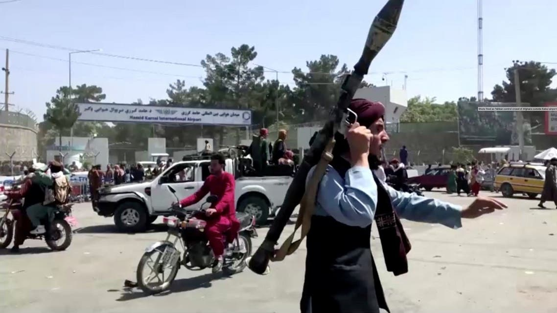 A Taliban fighter runs towards crowd outside Kabul airport, Kabul, Afghanistan, on August 16, 2021, in this still image taken from a video. (Reuters)