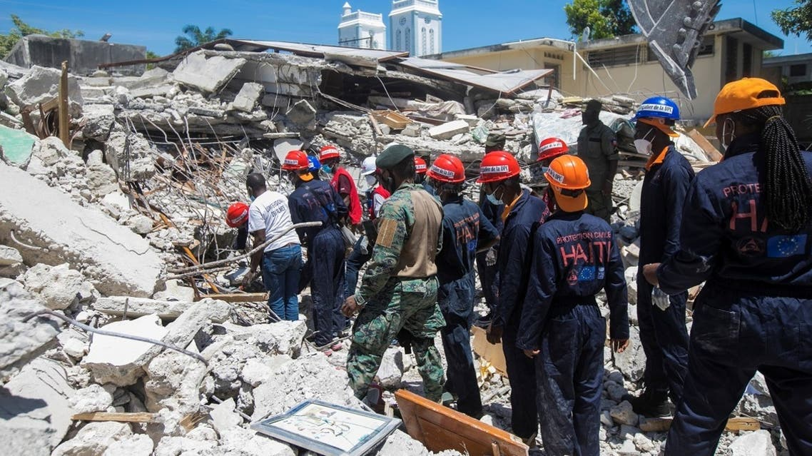 Members of a rescue and protection team clean debris from a house after a 7.2 magnitude earthquake in Les Cayes, Haiti August 15, 2021. (Reuters/Ralph Tedy Erol)