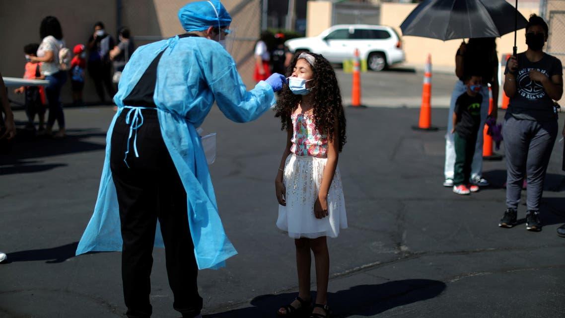 طفلة تخضع لفحص كورونا في أميركا (رويترز)