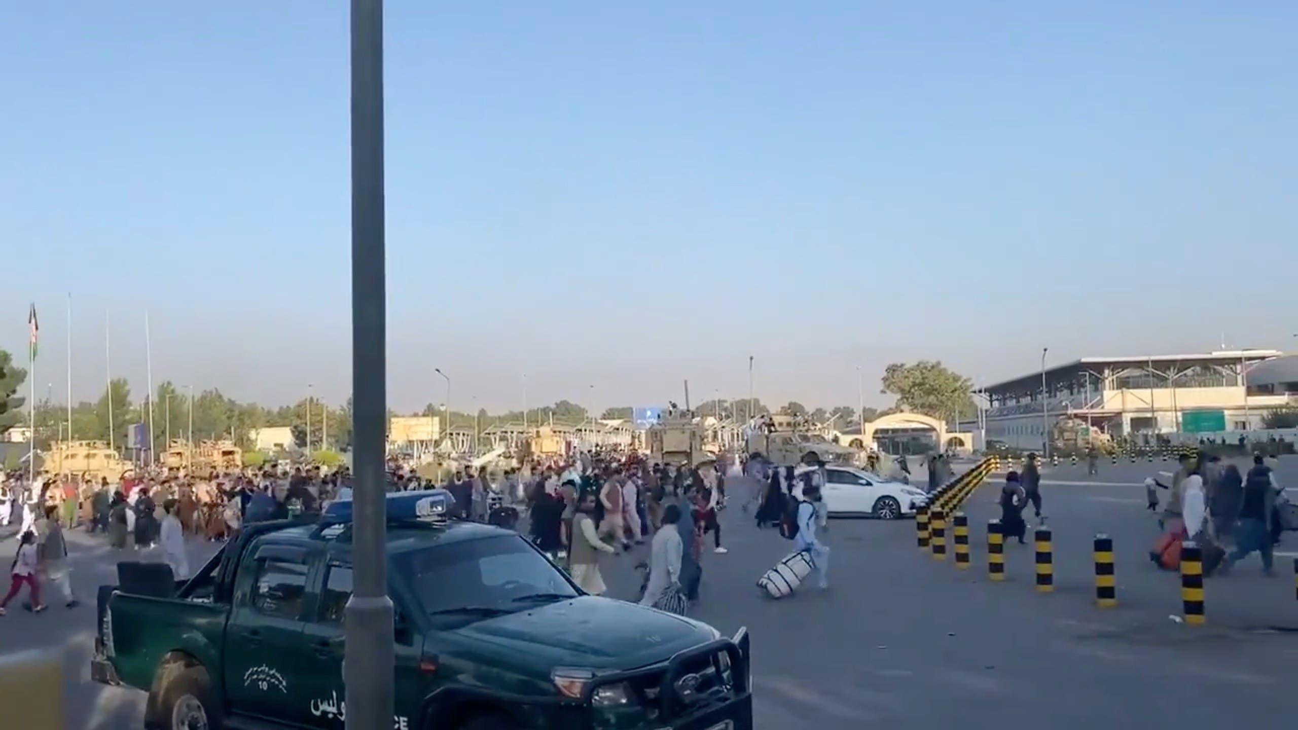 أشخاص يركضون نحو مطار كابل (رويترز)