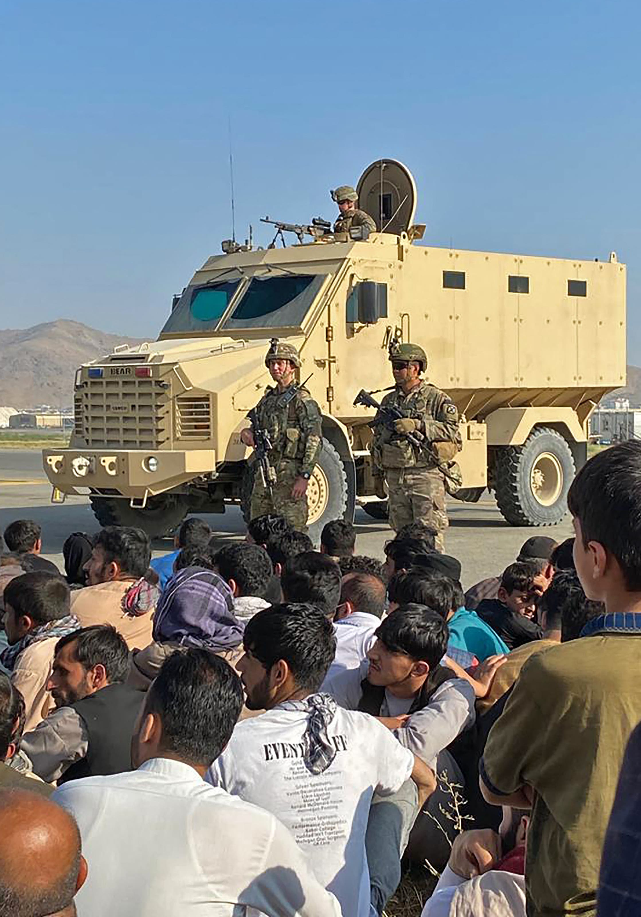 Afghans crowd at the airport as US soldiers stand guard in Kabul on August 16, 2021. (AFP)