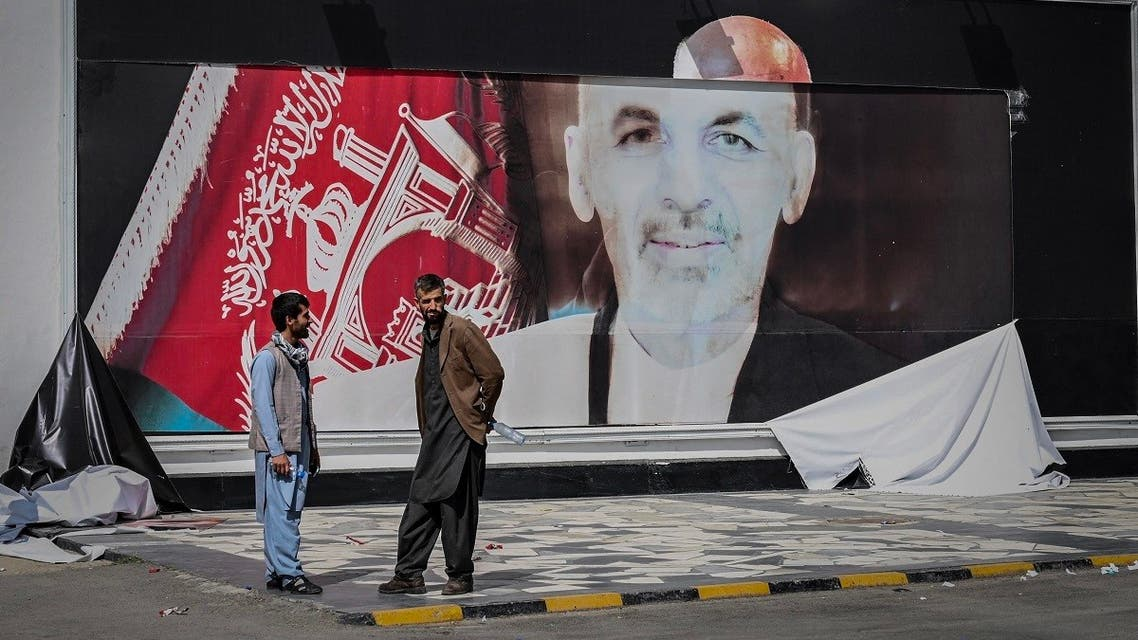 Afghan men stand next to a torn poster of Afghan President Ashraf Ghani at the Kabul airport in Kabul on August 16, 2021. (Wakil Kohsar/AFP)