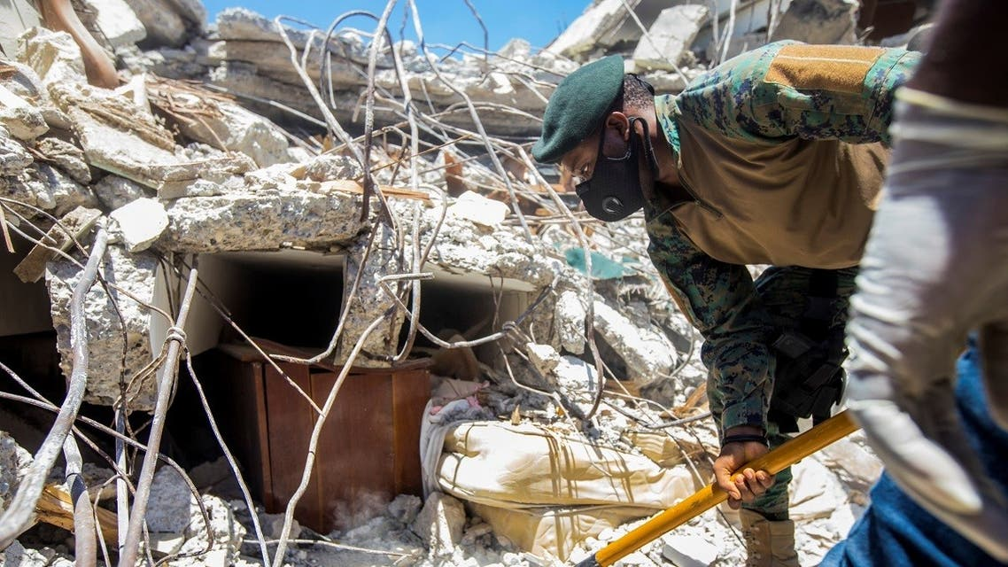 A soldier cleans debris from a house after a 7.2 magnitude earthquake in Les Cayes, Haiti August 15, 2021. (Reuters/Ralph Tedy Erol)