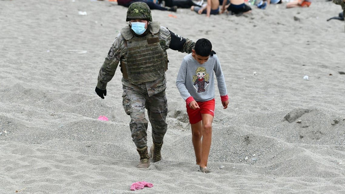A Spanish soldier walks with a migrant minor upon his arrival at the Spanish enclave of Ceuta, on May 18, 2021. (Antonio Sempere/AFP)