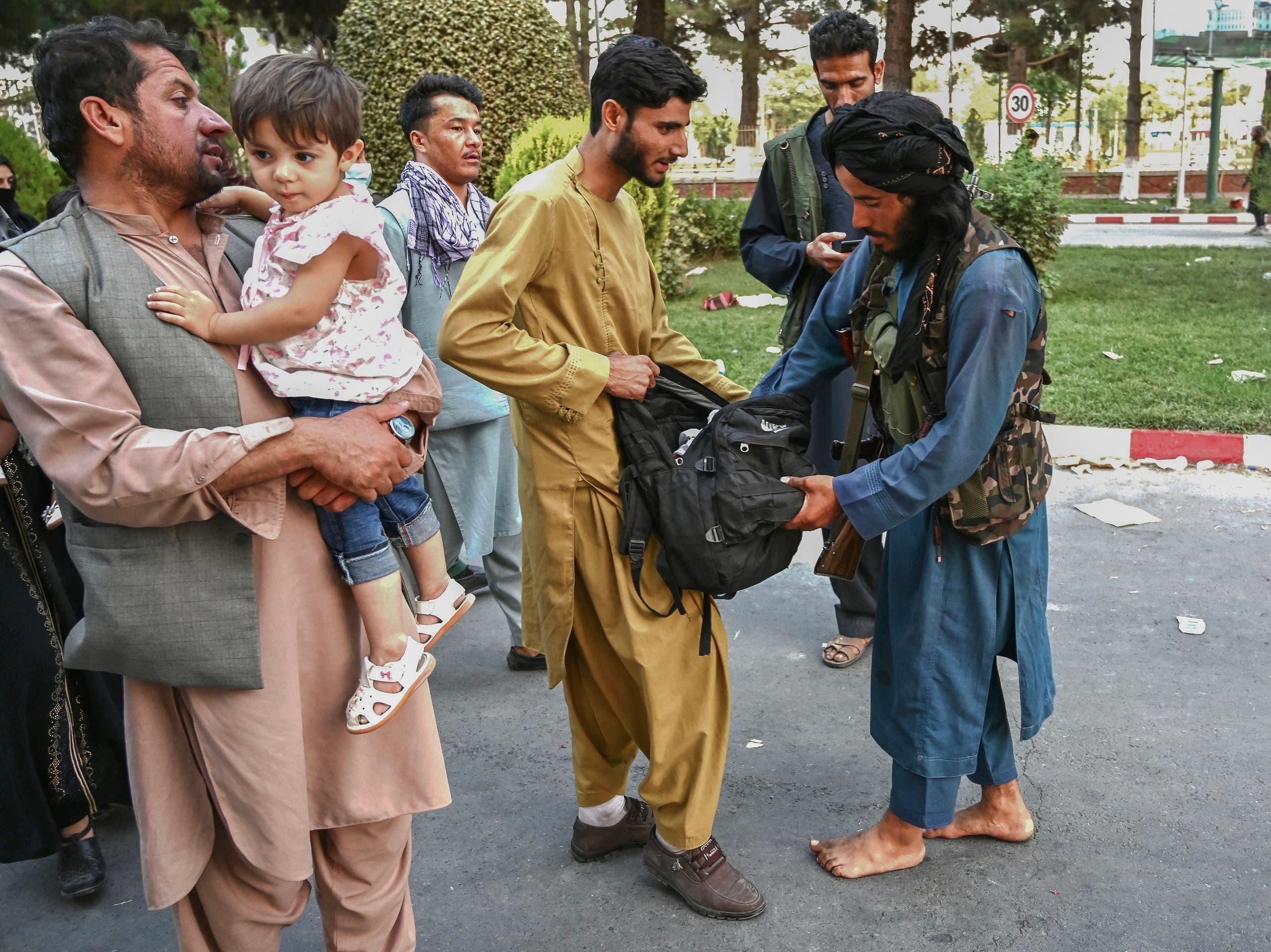عناصر من طالبان يفتشون المواطنين الخارجين من مطار كابل أمس