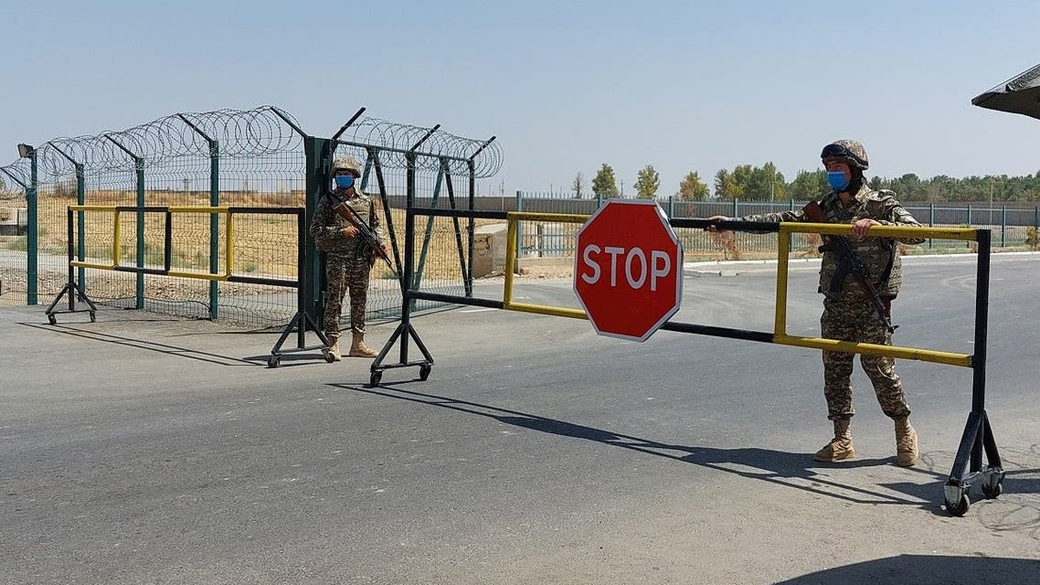 """Uzbek soldiers guard a checkpoint, two kilometers from """"Friendship Bridge"""" over the Amu Darya river, which separates Uzbekistan and Afghanistan near Termez on August 15, 2021. (Temur Ismailov/AFP)"""