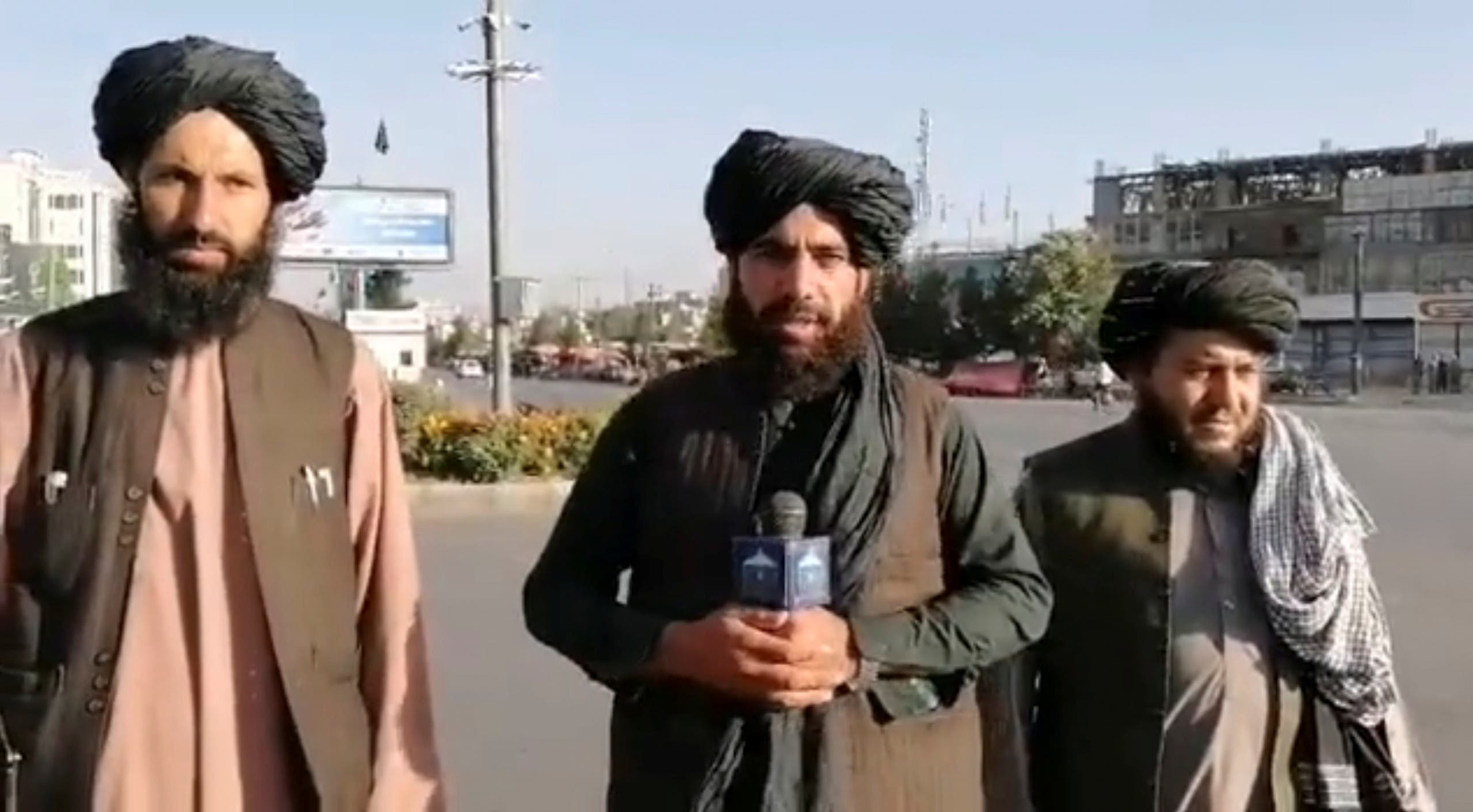 A man, who purportedly is a Taliban militant, holds a wireless microphone as he speaks on the street in Kabul, Afghanistan. (A still image taken from social media video uploaded August 16, 2021 and obtained by Reuters) .