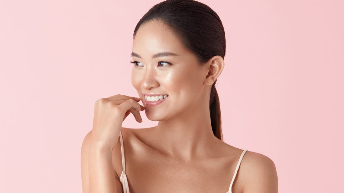 Woman. Beauty Asian Model Portrait. Smiling Female Touches Face And Looking Away. Beautiful Ethnic Girl With Healthy Smooth Skin And Nude Makeup Against Pink Background. stock photo