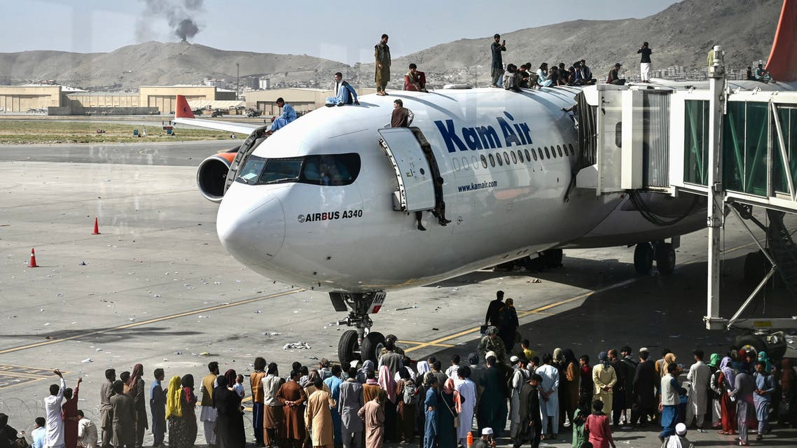 Afghan people climb atop a plane as they wait at the Kabul airport in Kabul on August 16, 2021. (AFP)