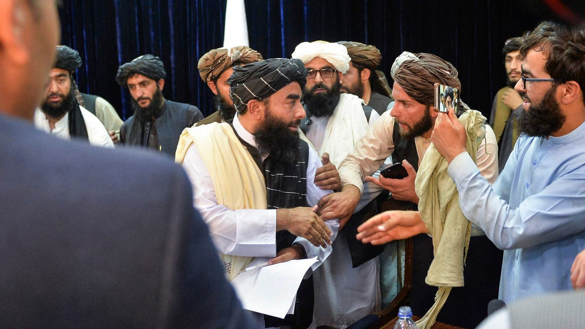 Taliban spokesperson Zabihullah Mujahid (C) leaves after addressing the first press conference in Kabul on August 17, 2021 following the Taliban stunning takeover of Afghanistan.
