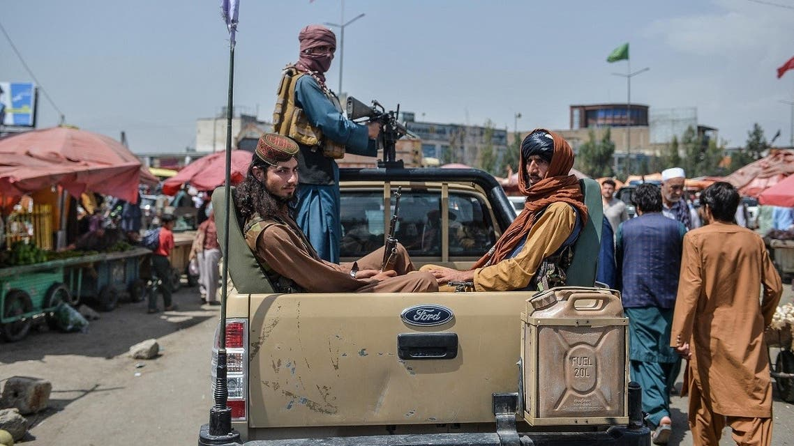 Taliban fighters on a pick-up truck move around a market area, flocked with local Afghan people at the Kote Sangi area of Kabul on August 17, 2021. (Hoshang Hashimi/AFP)