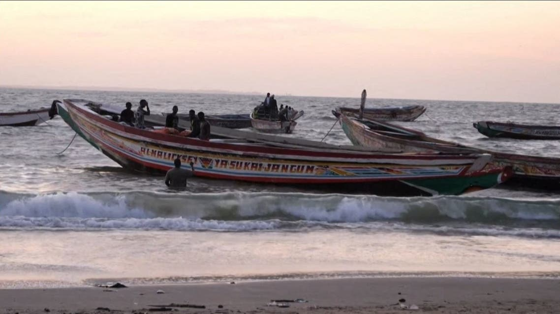 This image grab taken from an AFP video shows boats in the water at a beach, in Barra on December 5, 2019, after at least 62 people died on December 4, 2019 when their makeshift vessel capsized off the coast of Mauritania, including 52 migrants from Gambia. (Romain Chanson/AFPTV/AFP)