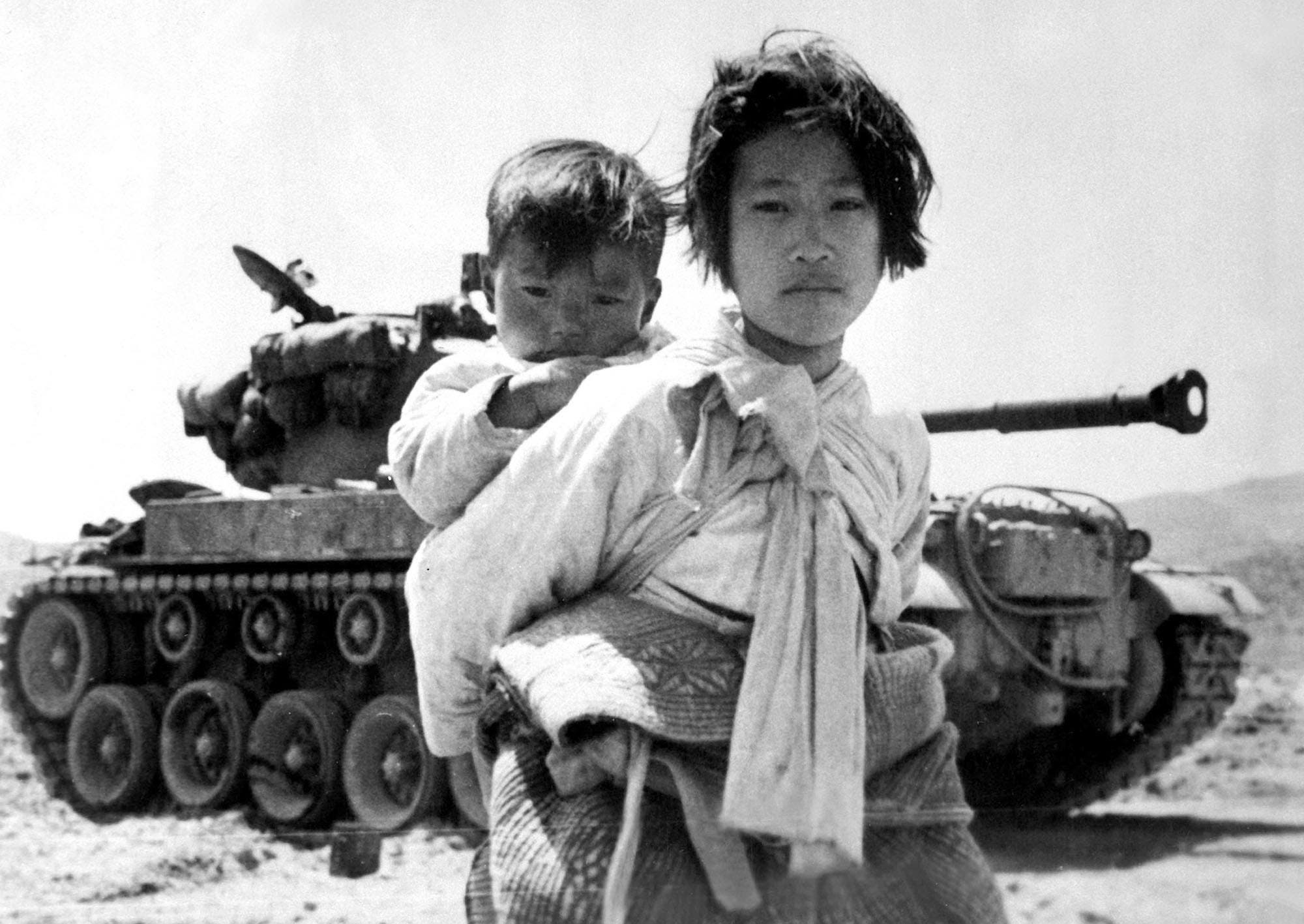 لاجئة من كوريا الجنوبية وهي تحمل شقيقها على ظهرها مع بداية الغزو الشمالي