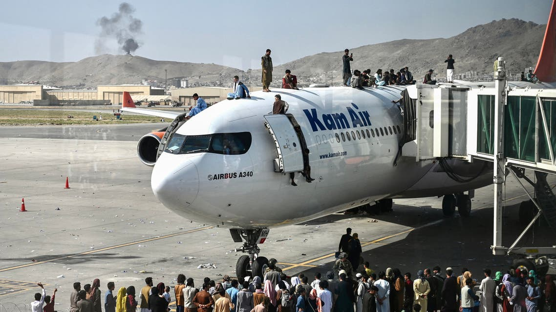 Afghan people climb atop a plane as they wait at the Kabul airport in Kabul on August 16, 2021, after a stunningly swift end to Afghanistan's 20-year war, as thousands of people mobbed the city's airport trying to flee the group's feared hardline brand of Islamist rule. (File photo: AFP)