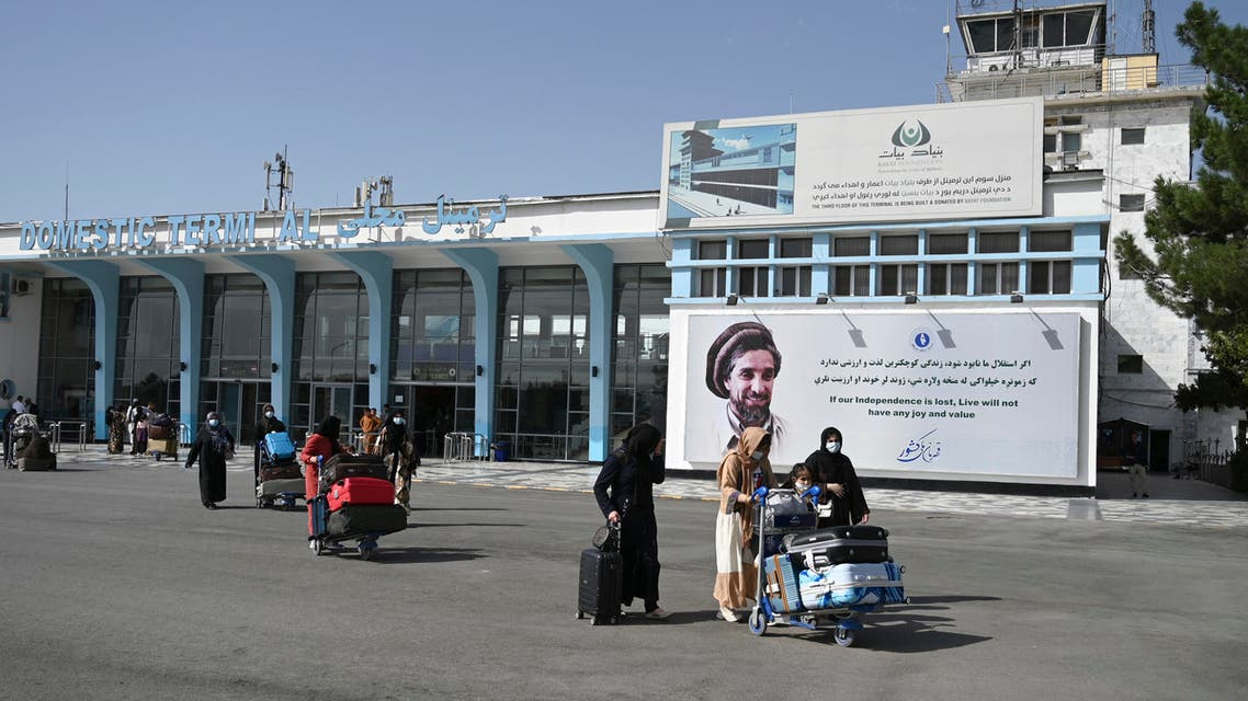 Afghan passengers carry their belongings as they come out from the domestic terminal, at the Kabul airport in Kabul on August 8, 2021.