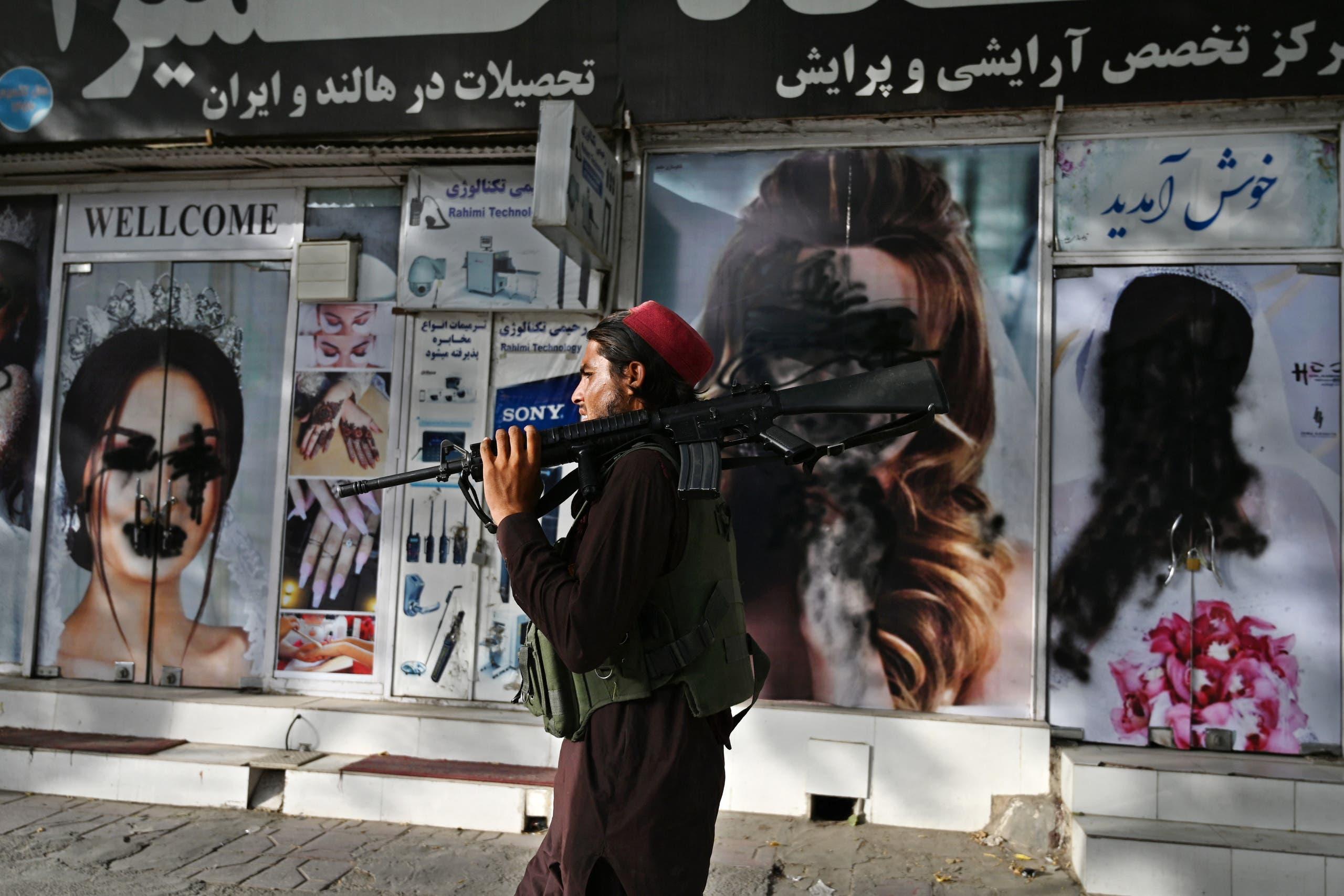 عنصر من طالبان يمر أمام صالون نسائي في كابل اليوم بعدما تم نزع صور النساء عن واجهته