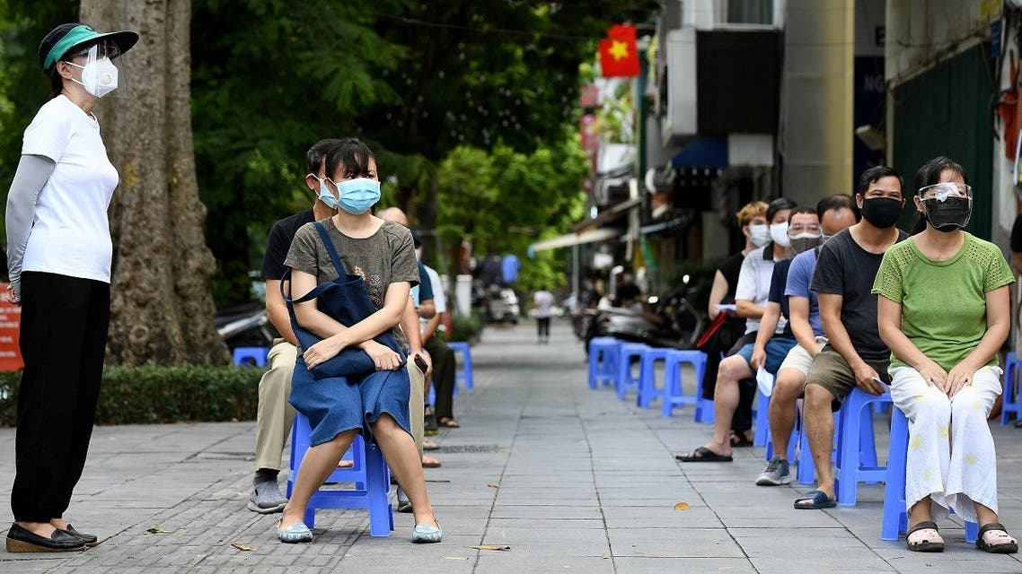 Residents wait to provide swab samples for Covid-19 testing along a street in Hanoi on August 18, 2021, amidst the government imposed two-week lockdown to stop the spread of the coronavirus. (AFP)