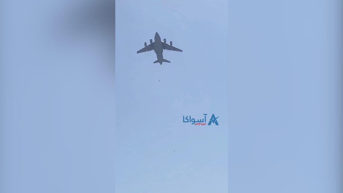 A U.S. Air Force plane flies overhead after social media videos showed people clinging to the plane on the tarmac at Kabul airport on August 16, 2021. (ASVAKA NEWS/via Reuters)