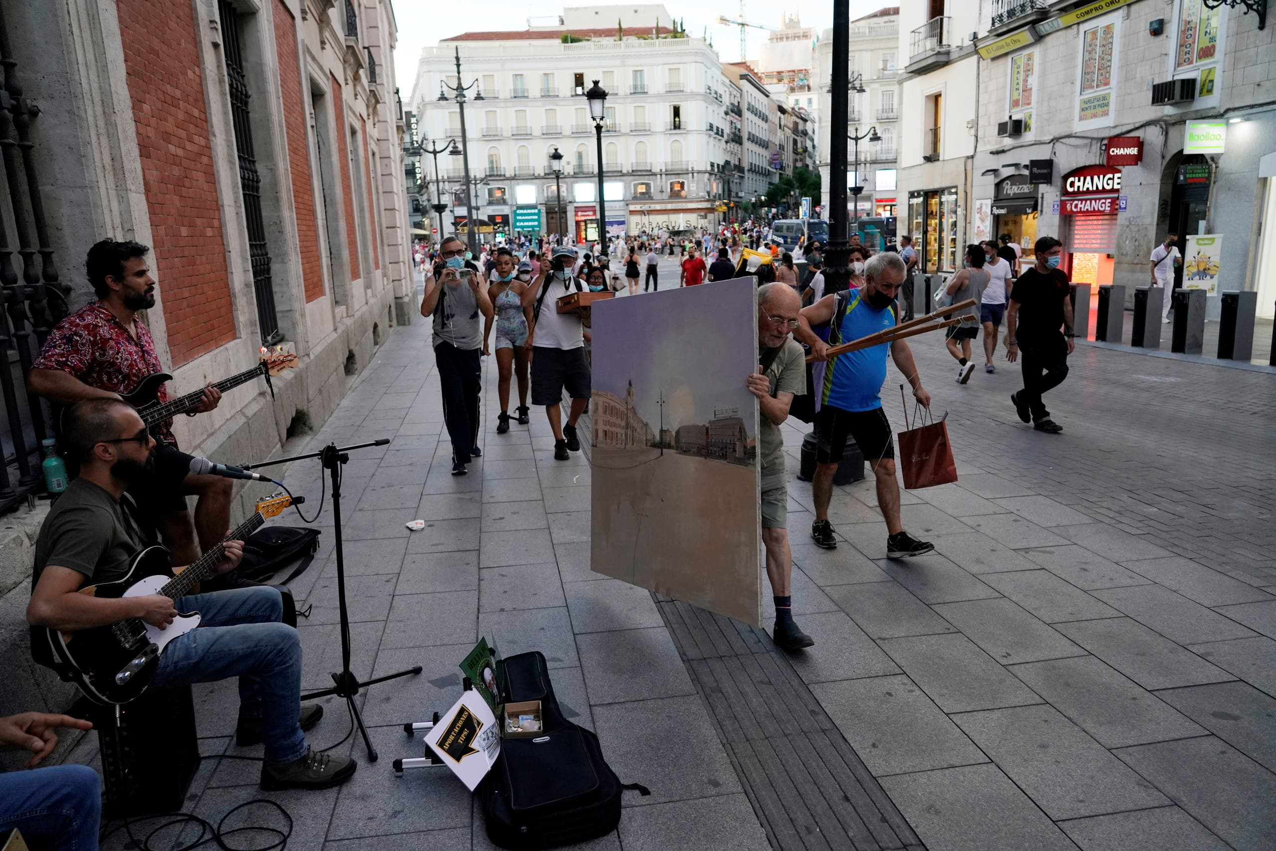 Spanish artist Antonio Lopez carries the canvas on which he is painting the famous Puerta del Sol square after a session in Madrid, Spain, August 5, 2021. Picture taken August 5, 2021. REUTERS/Juan Medina