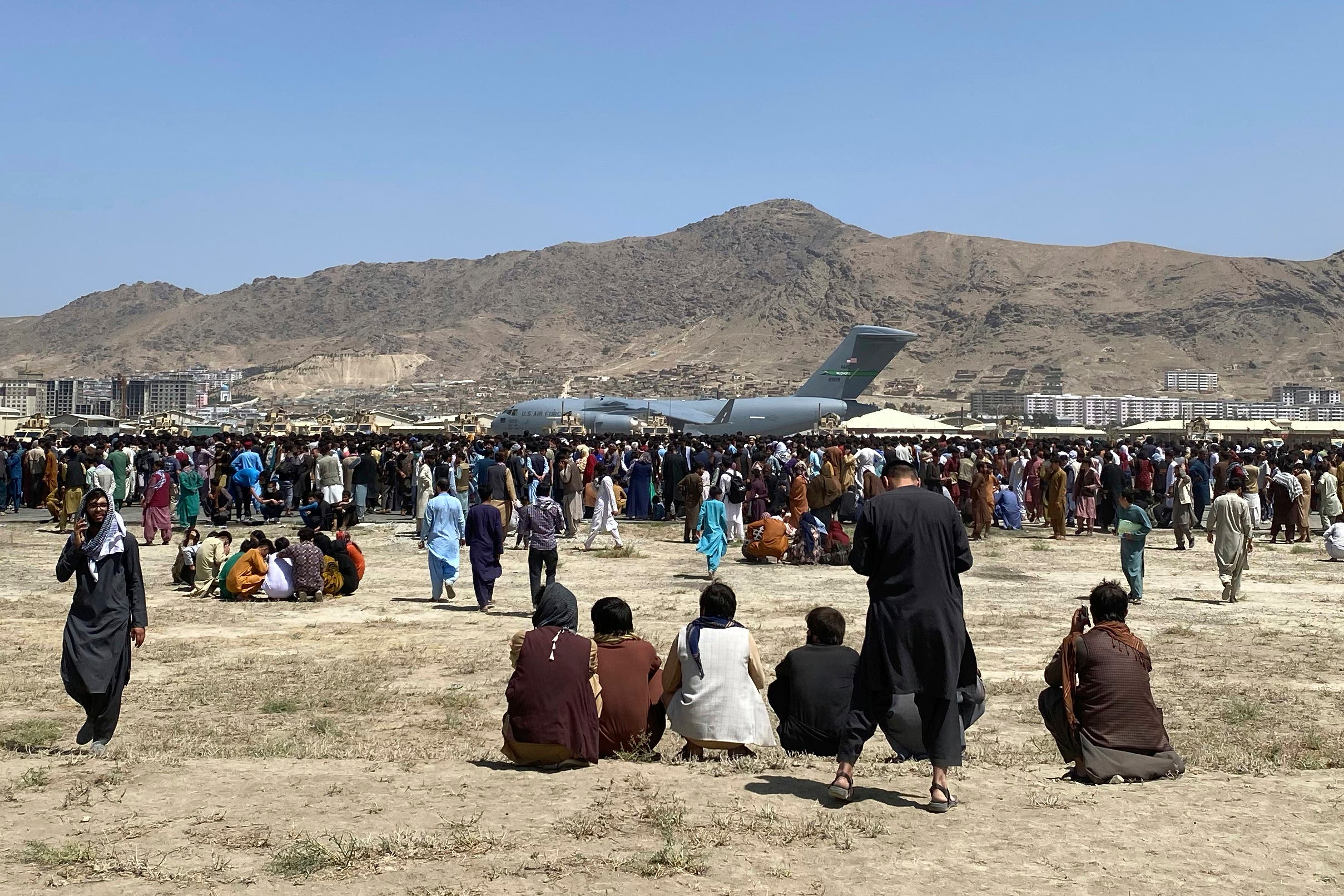 Hundreds of people gather near a US Air Force C-17 transport plane at a perimeter at the international airport in Kabul, Afghanistan, Monday, Aug. 16, 2021. (AP)