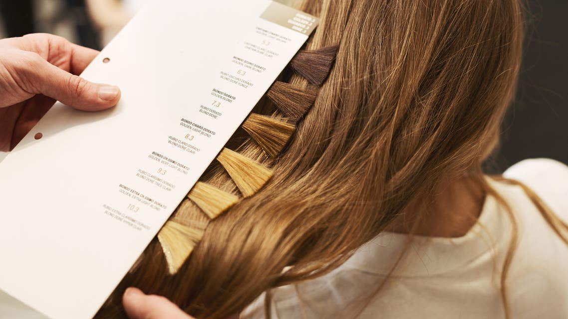 Stylist choosing color from hair samples for woman in salon stock photo