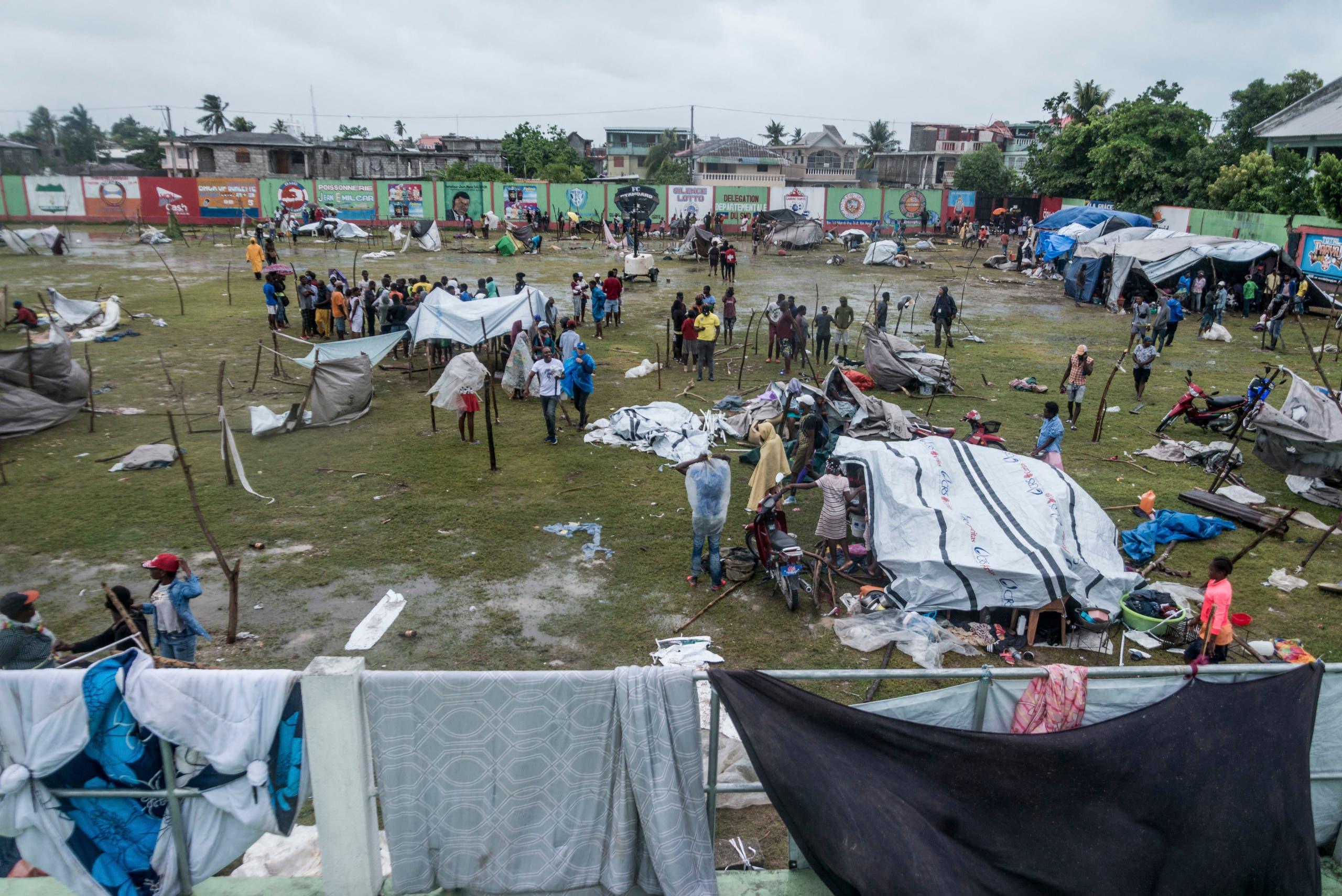سكان يحتمون من الأمطار بخيم بلاستيكية