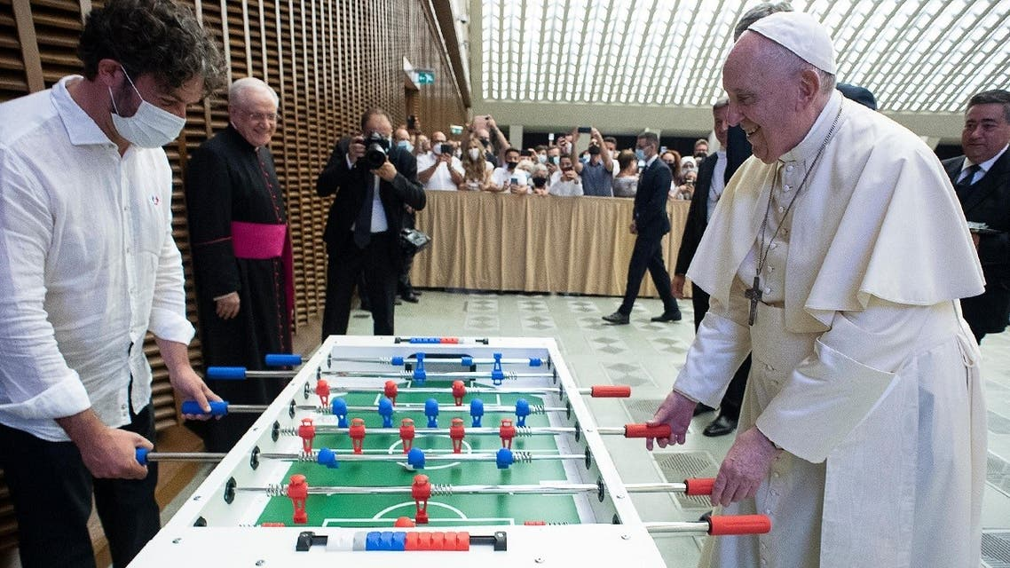 This handout photo taken on August 18, 2021, shows Pope Francis playing football table against Natale Tonini of the Tuscany table football amateur association on the sidelines of the weekly audience at The Vatican. (Handout/Vatican Media/AFP)